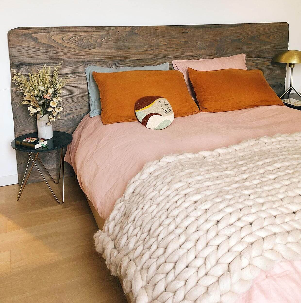 A double bed dressed with orange tones and a wooden headboard