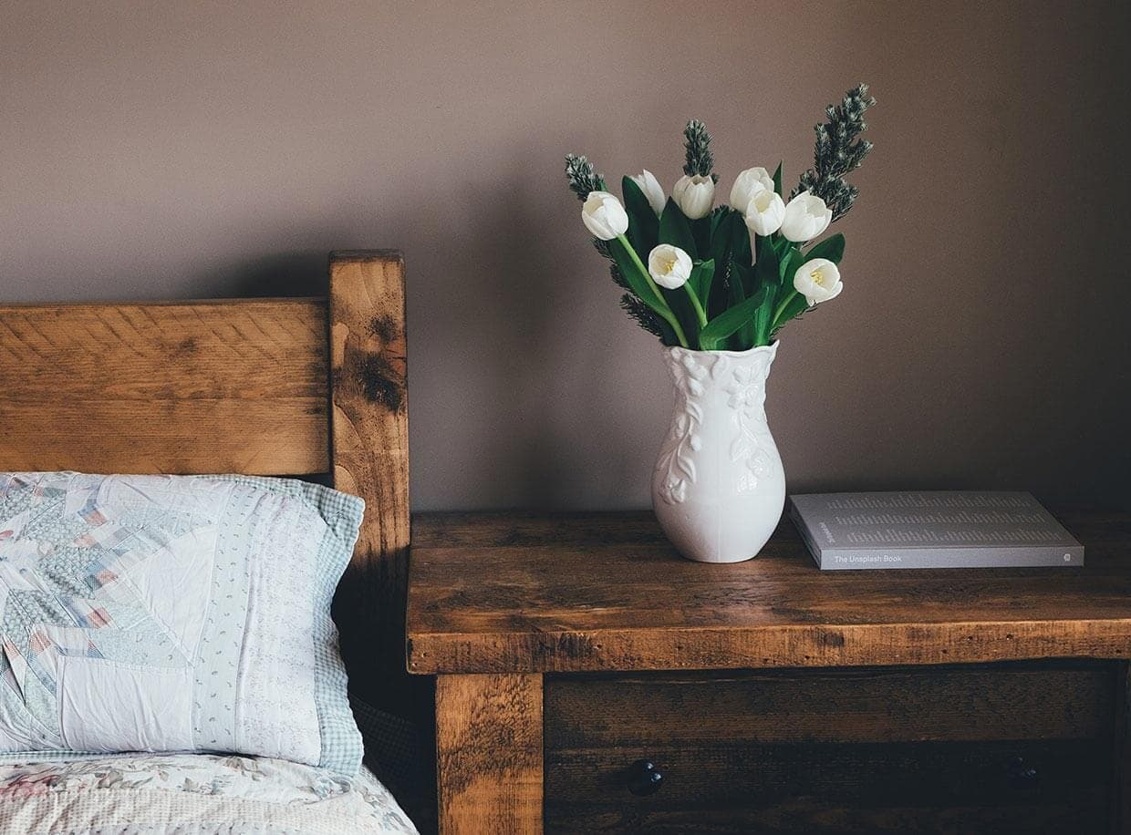 A wooden bedside table with a white vase filled with white tulips.