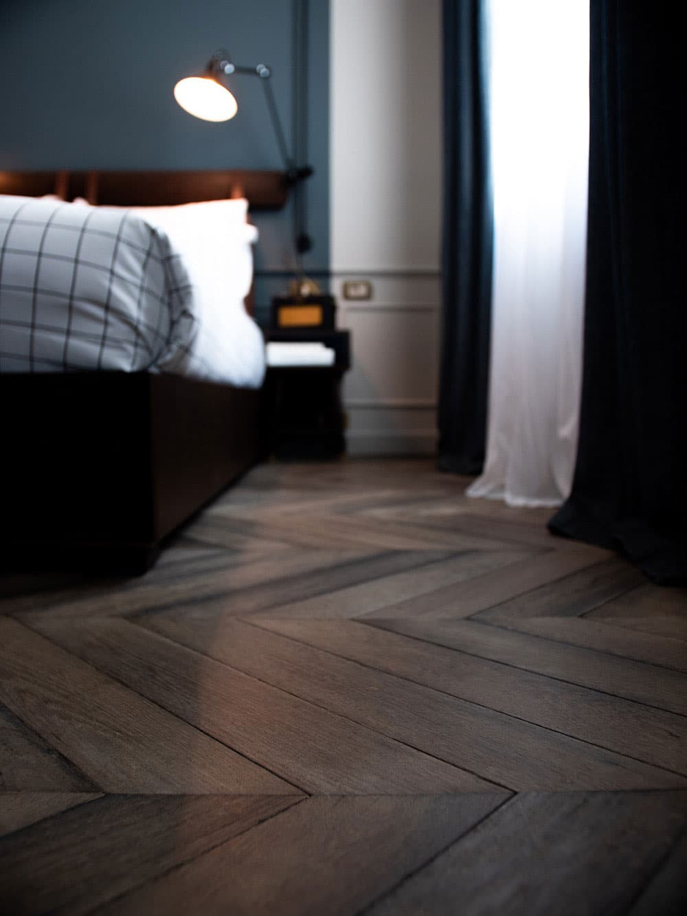 Wooden flooring with a low view of a bed that is lit up with a bedside light.