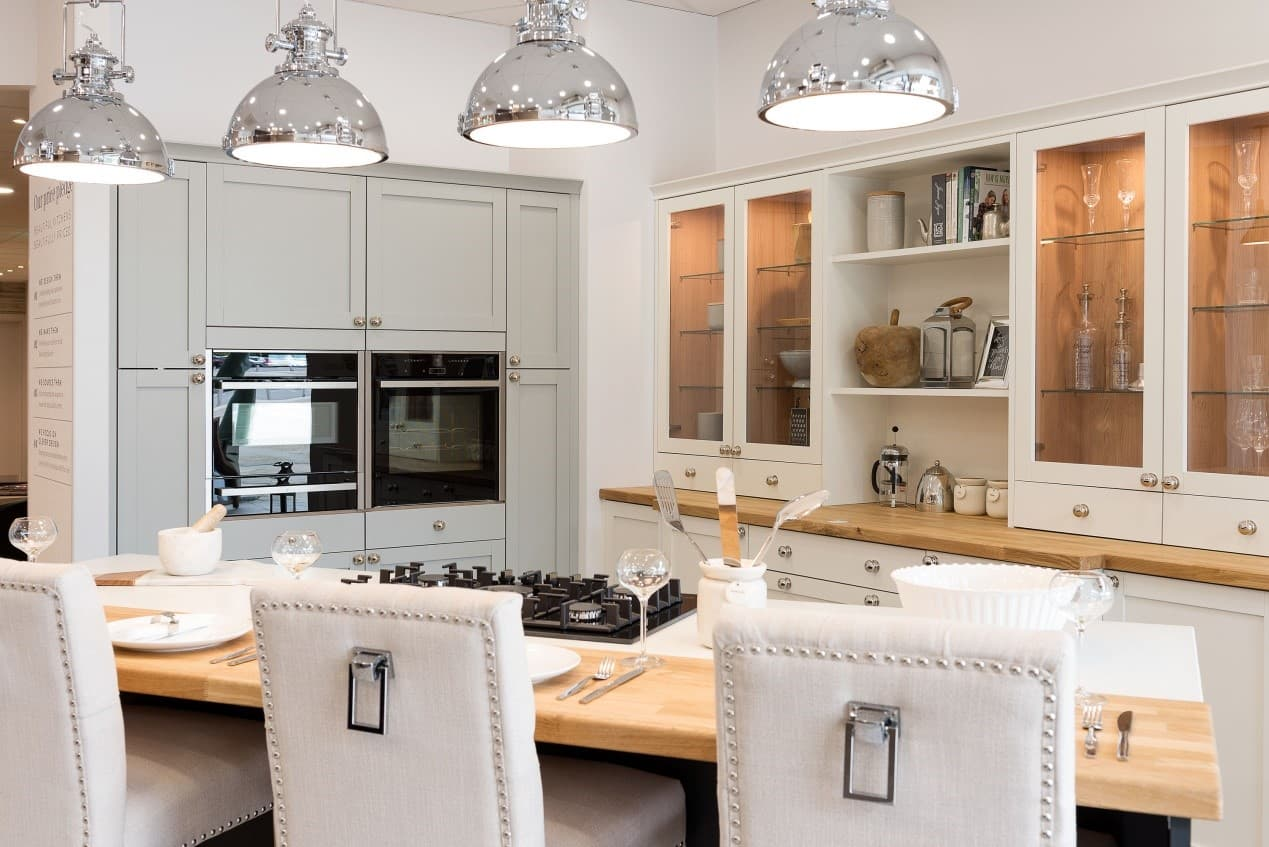 A pebble grey kitchen with white chairs, cabinets and breakfast bar