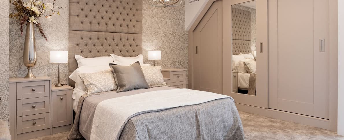 a bedroom with double bed and headboard with bedside tables, chandelier light and sliding wardrobes, with a mirror