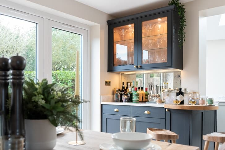Croft kitchen with drinks cabinet and bar stools with dining table in forefront